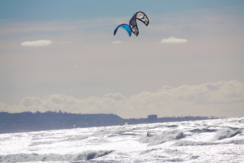 "Cardiff Reef is a ""no tangle"" zone. These two kitesurfers come pretty close but their pros and know what they're doing."